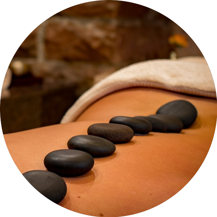 Heated black stones lined down a man's back during a hot stone massage.